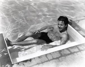 Dick Powell hanging out at the pool.